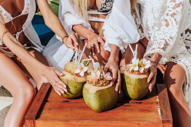 Amis détendant sur l'île Maldive, l'eau potable de noix de coco images stock