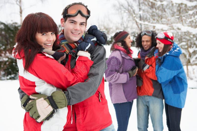 Amis d'adolescent ayant l'amusement dans la neige photo stock
