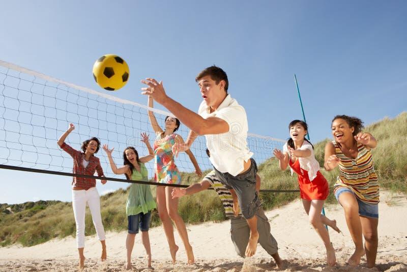 Amis d'adolescent jouant au volleyball sur la plage photographie stock libre de droits