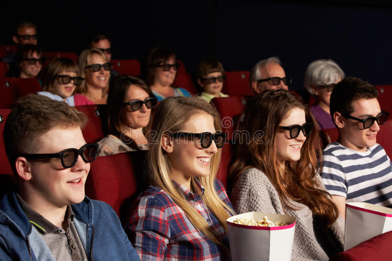 Amis d'adolescent observant le film 3D dans le cinéma photos stock