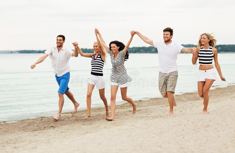 Amis dans des vêtements rayés fonctionnant le long de la plage photos stock