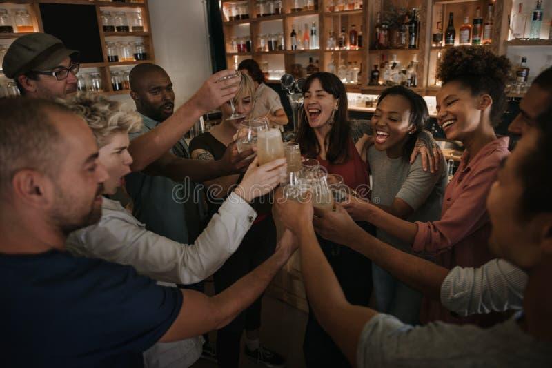 Amis dans une barre encourageant avec des boissons le soir photos stock
