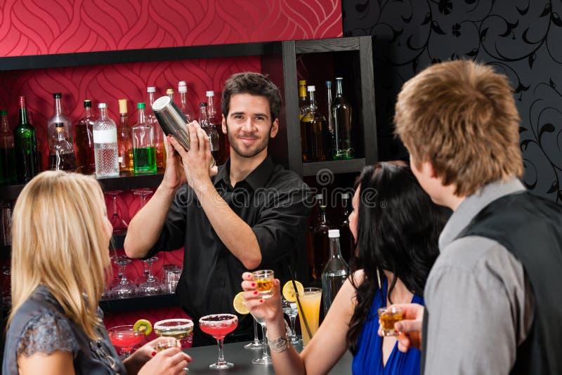 Amis de dispositif trembleur de cocktail de barman buvant au bar photo libre de droits