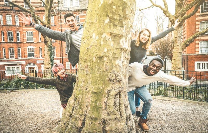 Amis de fantaisie multiraciaux ayant l'amusement dehors au parc de ville images libres de droits