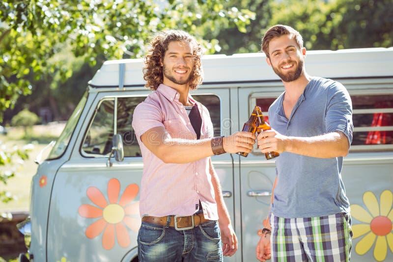 Amis de hippie grillant avec des bières images stock