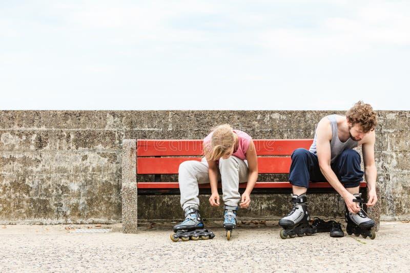 Amis de personnes mettant sur des patins de rouleau extérieurs images libres de droits