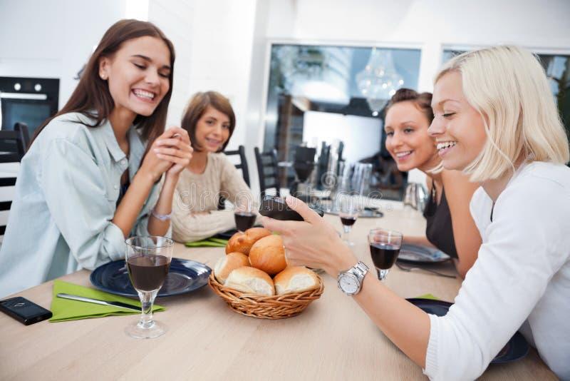 Amis de sourire à la table de salle à manger photo stock