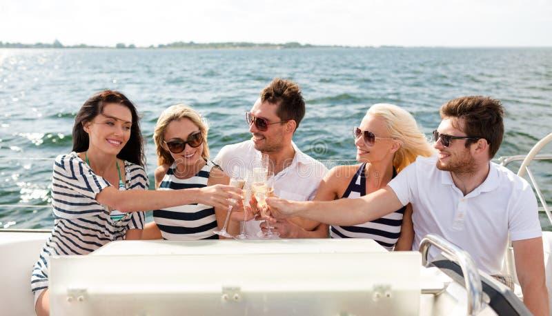 Amis de sourire avec des verres de champagne sur le yacht photographie stock libre de droits