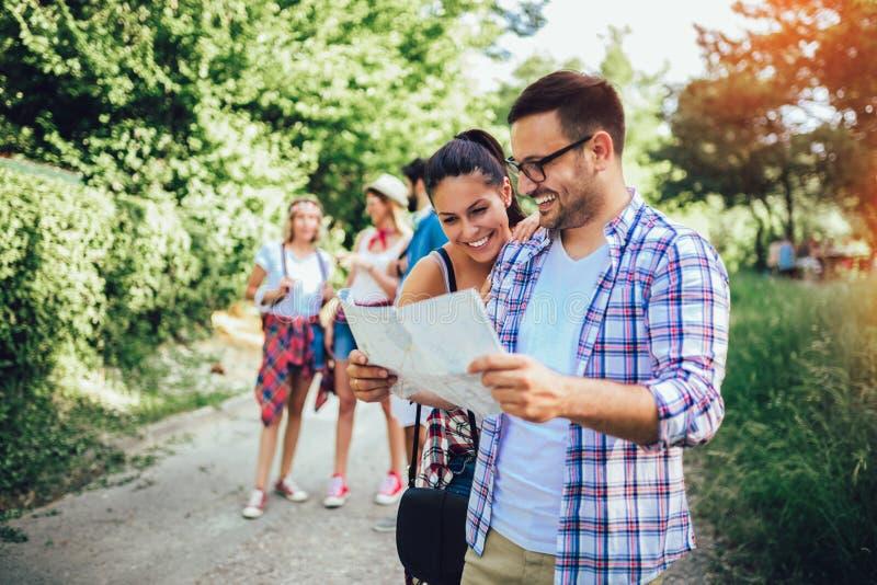 Amis de sourire marchant avec des sacs à dos en bois - aventure, voyage, tourisme, hausse et concept de personnes photo libre de droits