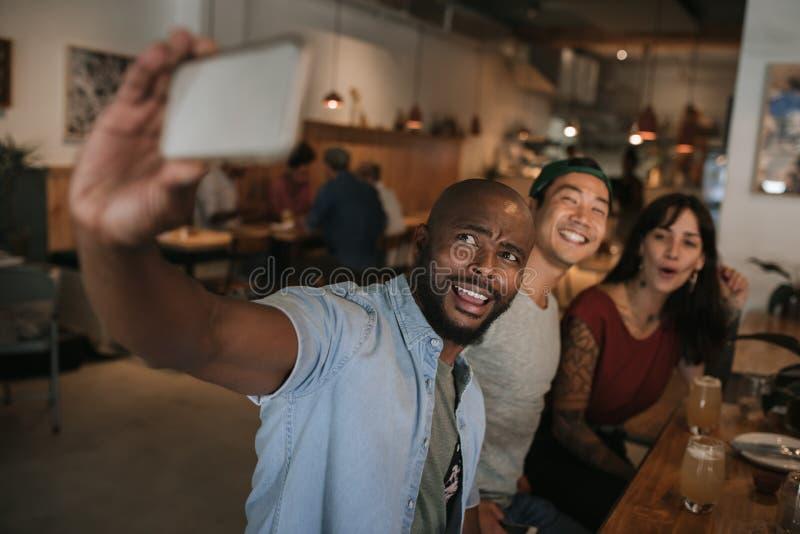 Amis de sourire prenant des selfies ensemble dans une barre images stock