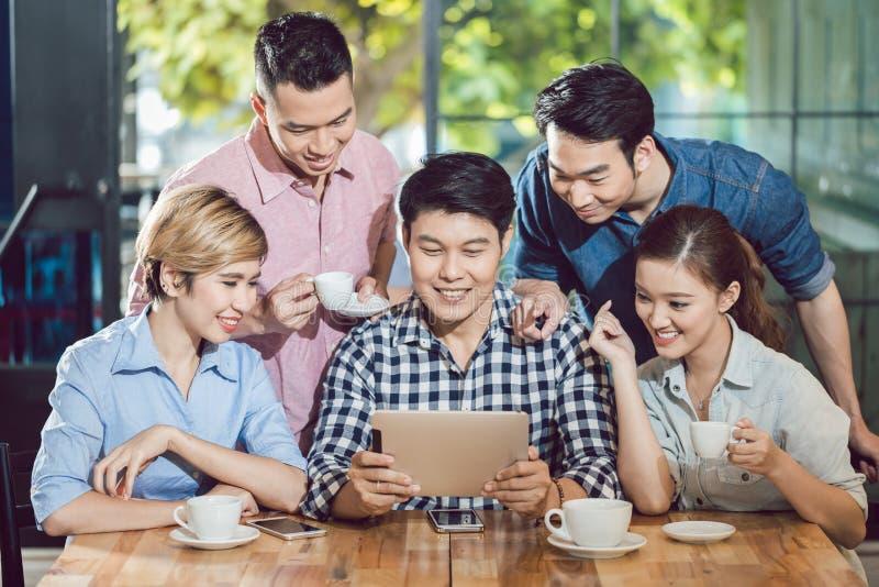 Amis de sourire regardant le comprimé numérique dans le café photos libres de droits