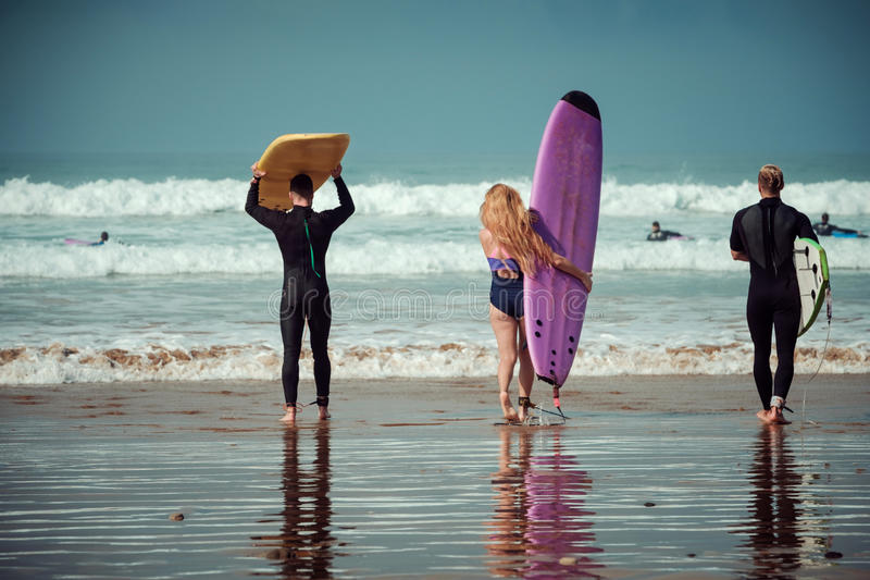Amis de surfer sur une plage avec conseils surfants photographie stock libre de droits