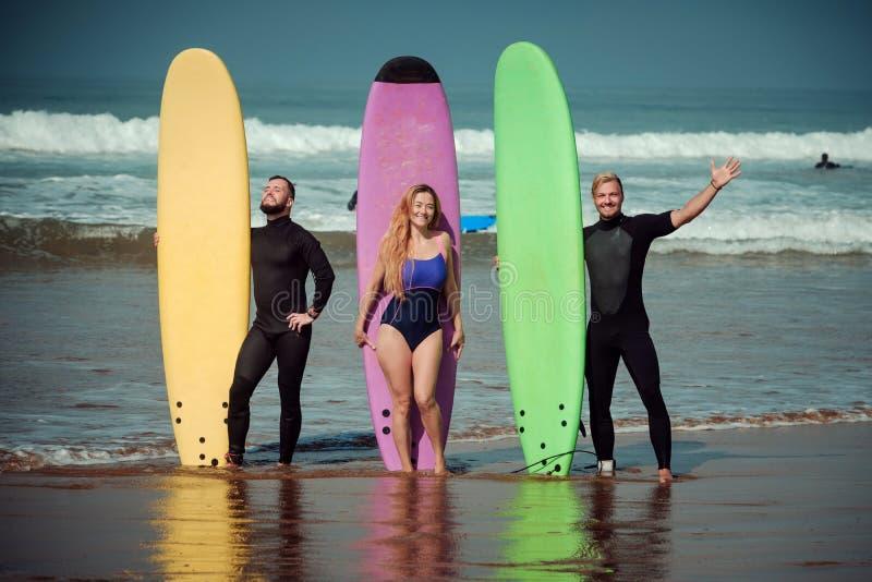 Amis de surfer sur une plage avec conseils surfants images libres de droits