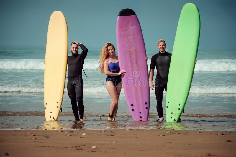 Amis de surfer sur une plage avec conseils surfants photos stock