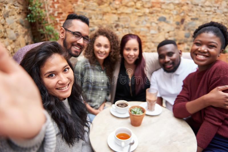 Amis divers prenant des selfies dans une cour à la mode de café photos stock