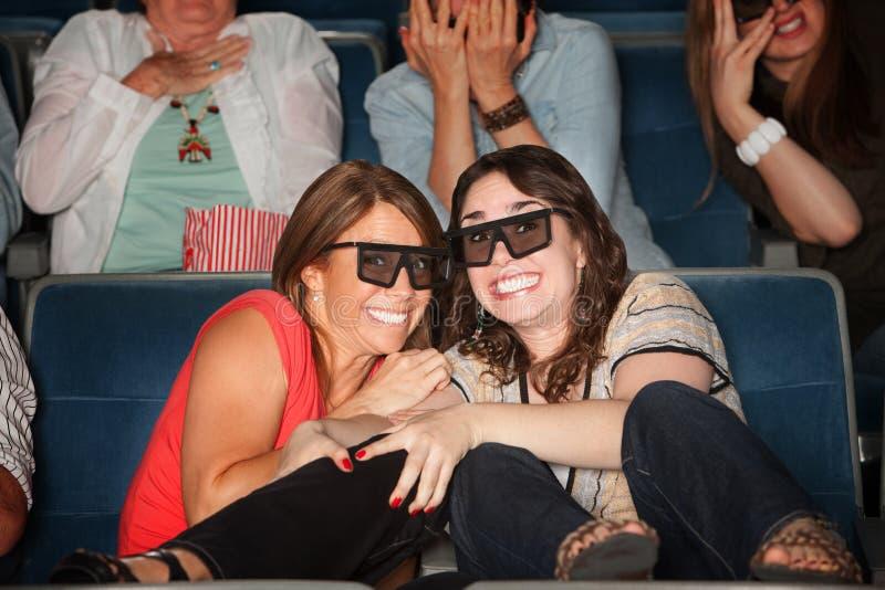Amis effrayés dans des sièges de théâtre photo stock