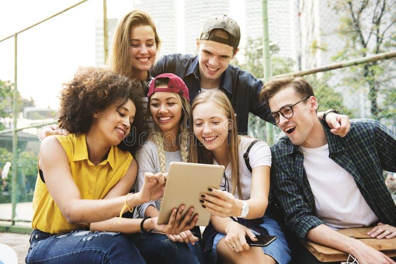 Amis en parc utilisant un comprimé numérique millénaire et la jeunesse image stock