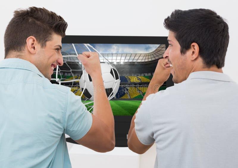 Amis encourageant tout en regardant le match de football à la télévision image stock