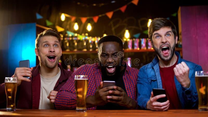 Amis enthousiastes se réjouissant la course de cheval de observation et faisant des paris en ligne, revenu image stock