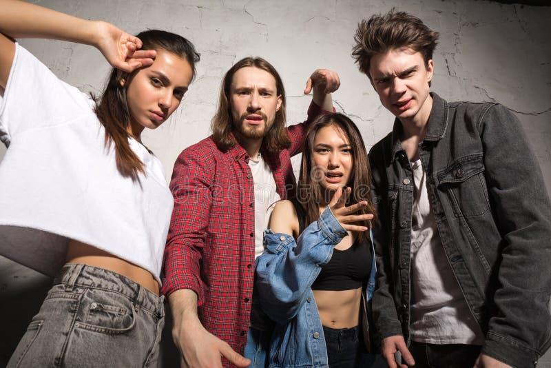 Amis fâchés de hippies se tenant au-dessus du fond gris photos libres de droits
