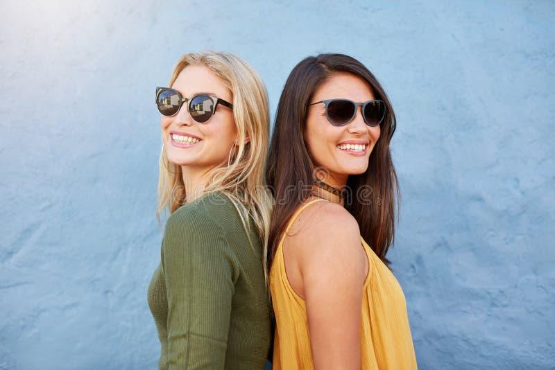 Amis féminins élégants utilisant des lunettes de soleil image libre de droits