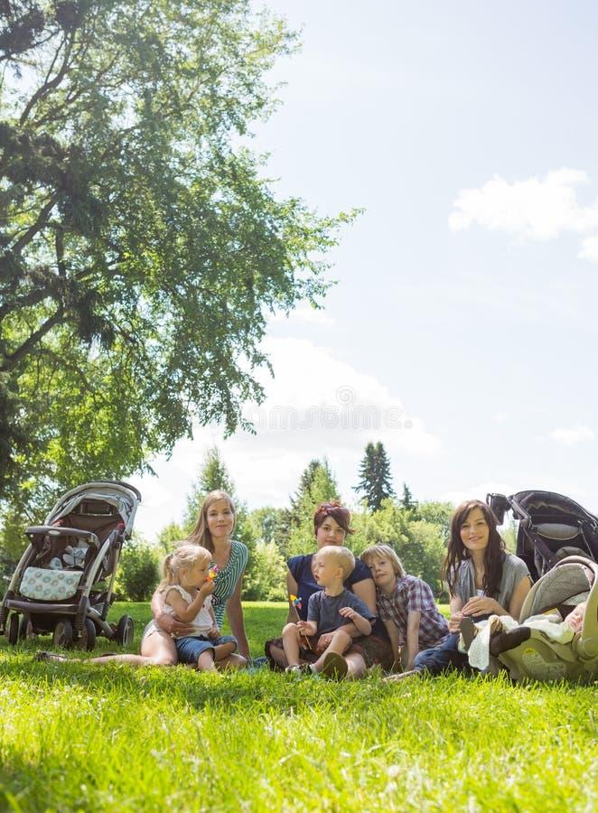 Amis féminins avec leurs enfants appréciant le pique-nique images stock