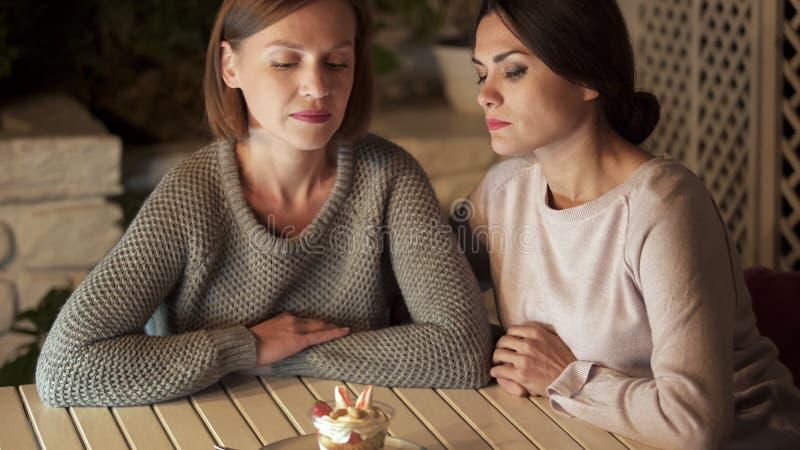 Amis féminins décidant d'éviter de manger les desserts sucrés, regardant le plat, régime photographie stock