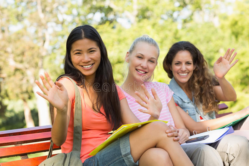 Amis féminins d'université s'asseyant sur le banc de campus photo stock