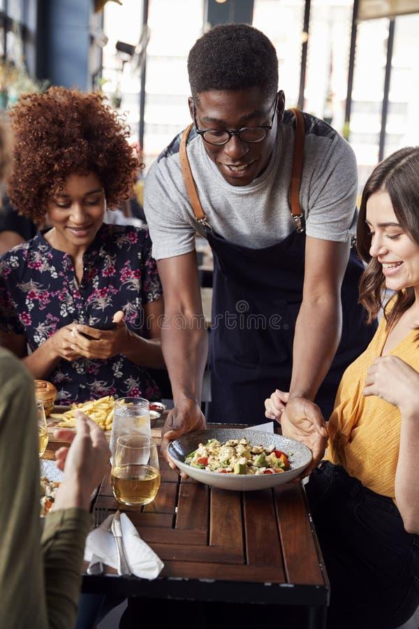 Amis féminins de Serving Group Of de serveur se réunissant pour les boissons et la nourriture dans le restaurant photographie stock