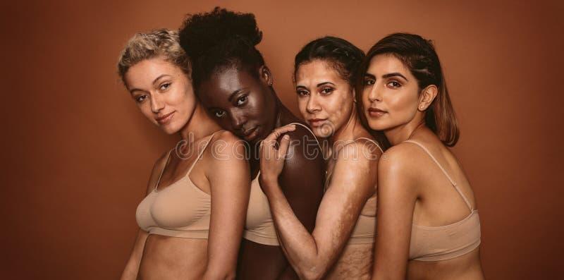 Amis féminins ethniques multi se tenant ensemble images stock