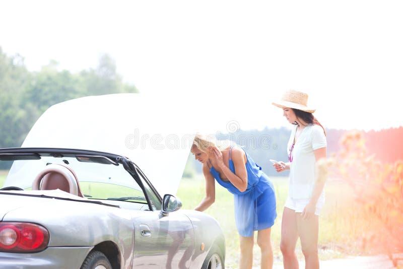 Amis féminins examinant la voiture décomposée sur la route de campagne photo libre de droits