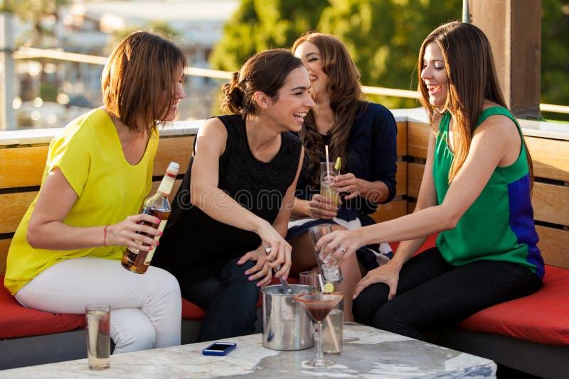 Amis féminins mignons ayant des boissons photographie stock