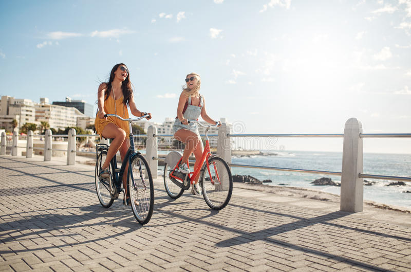 Amis féminins montant leurs bicyclettes sur la promenade photos stock
