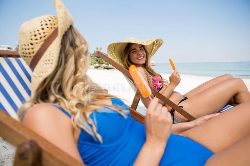 Amis féminins parlant tout en se reposant avec des glaces à l'eau sur la chaise de plate-forme image stock