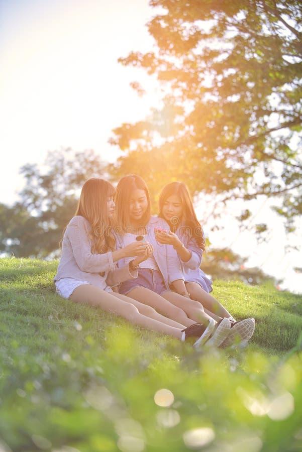 Amis féminins riant et regardant le téléphone portable images libres de droits