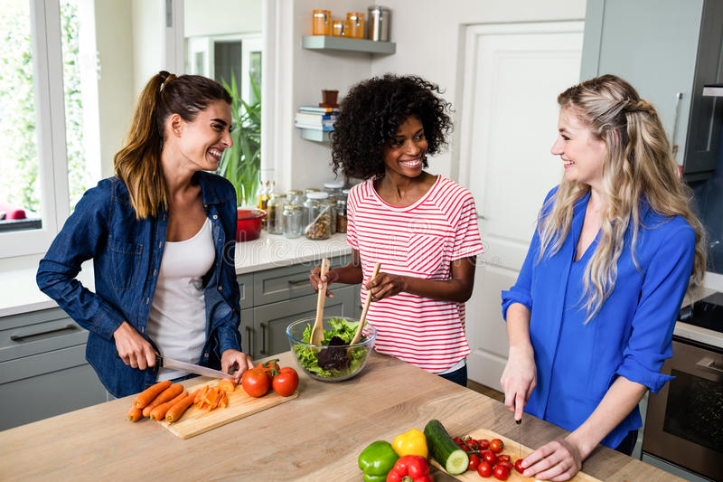 Amis féminins souriant tout en préparant la nourriture dans la cuisine photo stock