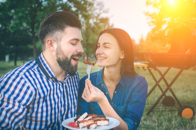 Amis faisant le barbecue et prenant le déjeuner dans la nature Couplez avoir l'amusement tout en mangeant et en buvant à un pique photos stock
