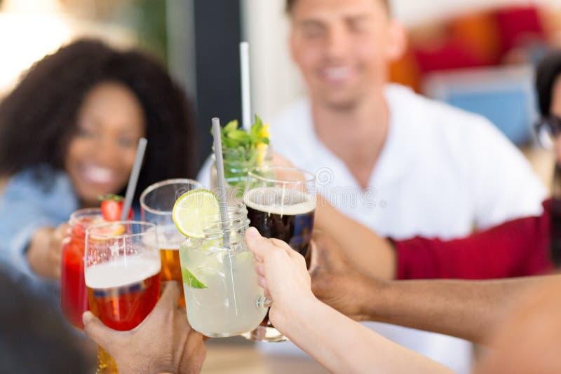 Amis faisant tinter des verres à la barre ou au restaurant image stock