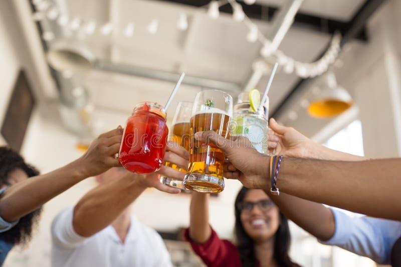 Amis faisant tinter des verres à la barre ou au restaurant photos libres de droits