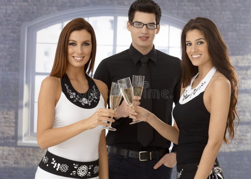 Amis faisant tinter la cannelure de champagne photos stock