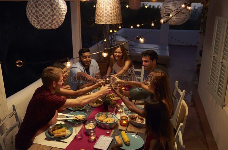 Amis faisant un pain grillé à un dîner sur un patio, Ibiza images stock