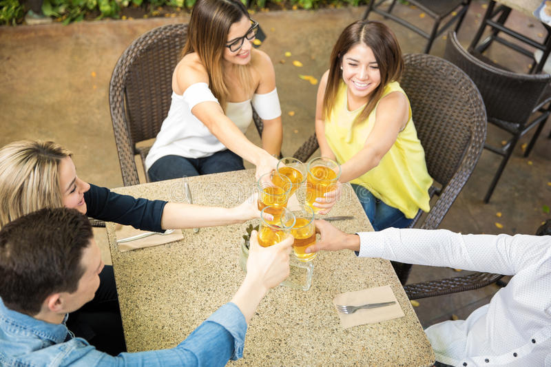 Amis faisant un pain grillé avec de la bière images libres de droits