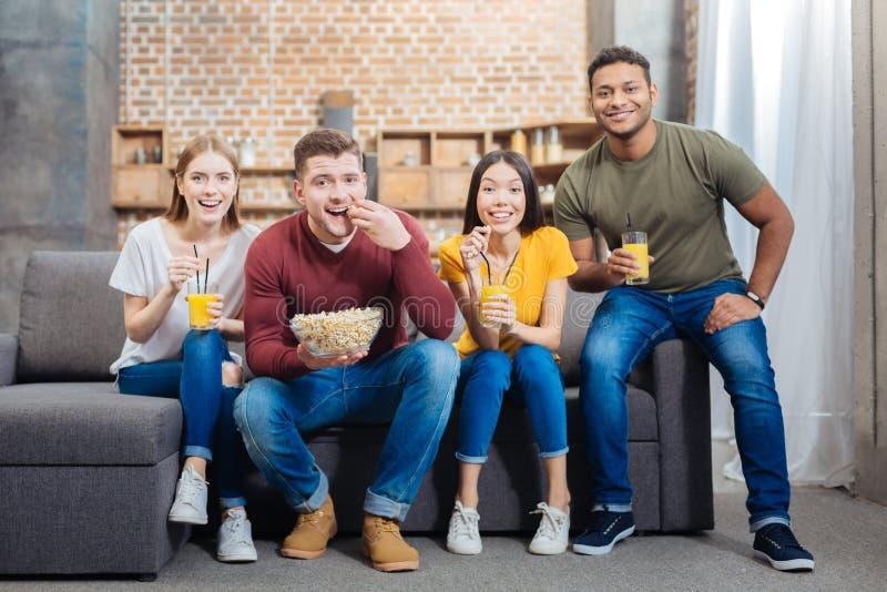 Amis gais buvant du jus et mangeant du maïs éclaté tout en observant un film photo libre de droits