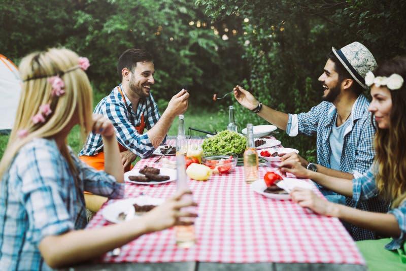 Amis gais s'asseyant à la table et ayant le repas photos stock