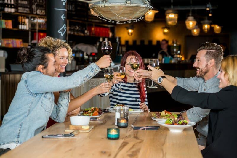 Amis grillant des verres à vin au restaurant image stock