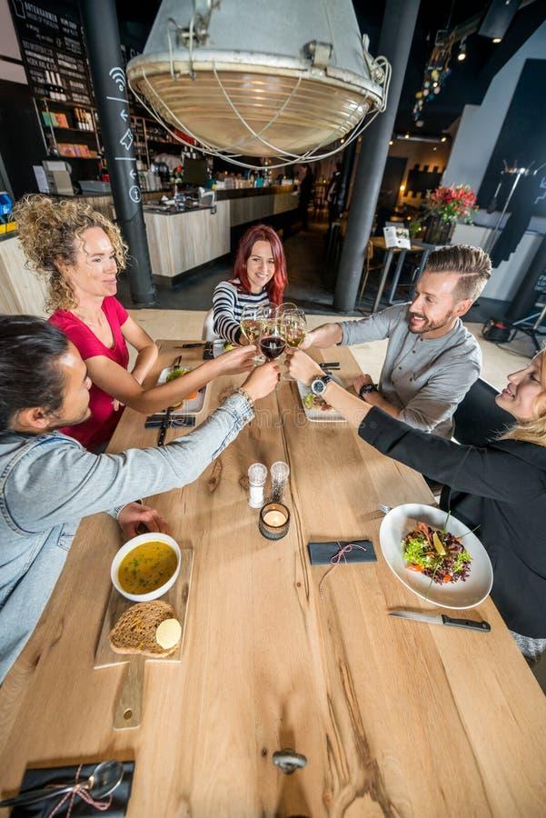 Amis grillant des verres à vin au Tableau image stock