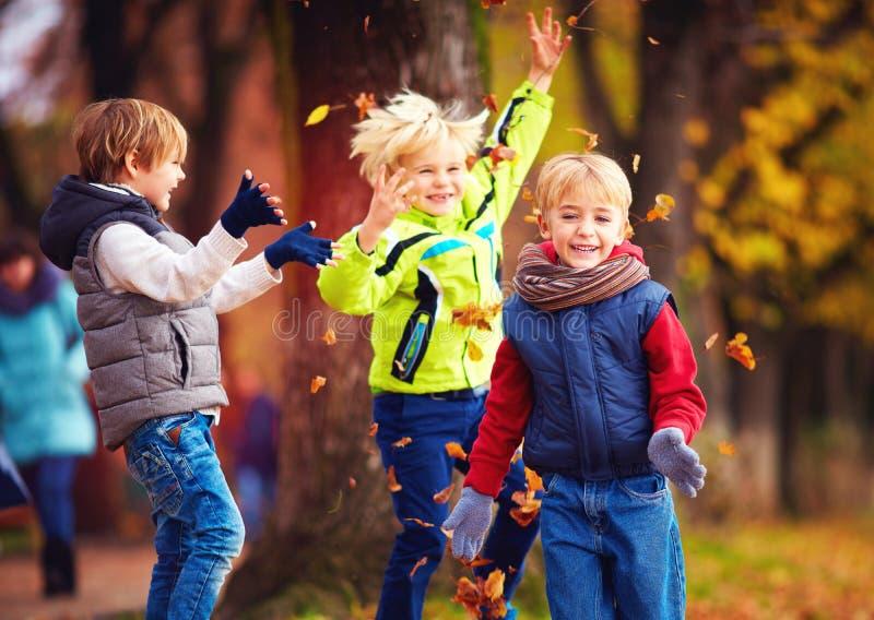 Amis heureux, écoliers ayant l'amusement dans le parc d'automne parmi les feuilles tombées photographie stock