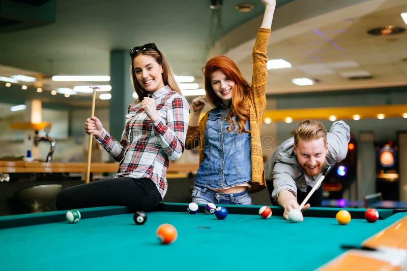 Amis heureux appréciant jouant la piscine image libre de droits