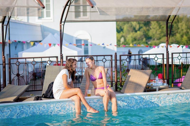 Amis heureux appréciant l'été à la réception au bord de la piscine de natation photos libres de droits