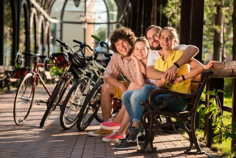 Amis heureux avec des bicyclettes en parc photos libres de droits